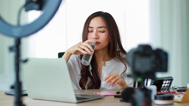 Messa a fuoco selettiva sulla fotocamera, giovane e bella ragazza asiatica che tiene in mano una bottiglia di lozione liquida e la annusa mostrando alla fotocamera durante la registrazione video trasmessa sul contenuto e la revisione dei cosmetici.