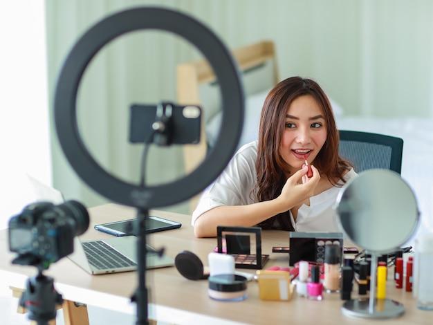 Messa a fuoco selettiva sulla fotocamera, la giovane e bella ragazza asiatica mostra il trucco come usare il rossetto sulla fotocamera con un sorriso e felice durante la registrazione video trasmessa sul contenuto e la revisione dei cosmetici.