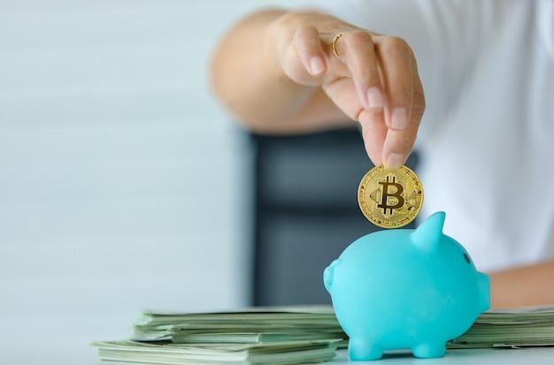 Messa a fuoco selettiva sulla moneta, una mano che tiene il simbolo del denaro bitcoin e metterlo in una scatola salvadanaio. concetto di tesoro di criptovaluta e investimento per il futuro.