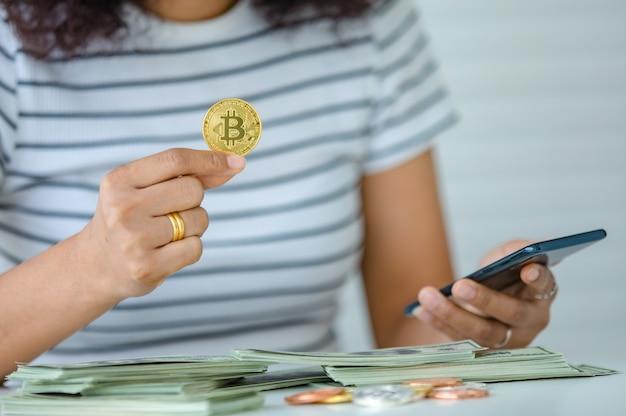 Messa a fuoco selettiva su una moneta, donna che tiene denaro bitcoin e utilizza uno smartphone con una pila di banconote su una scrivania. concetto di investimento in criptovaluta e risorse digitali.