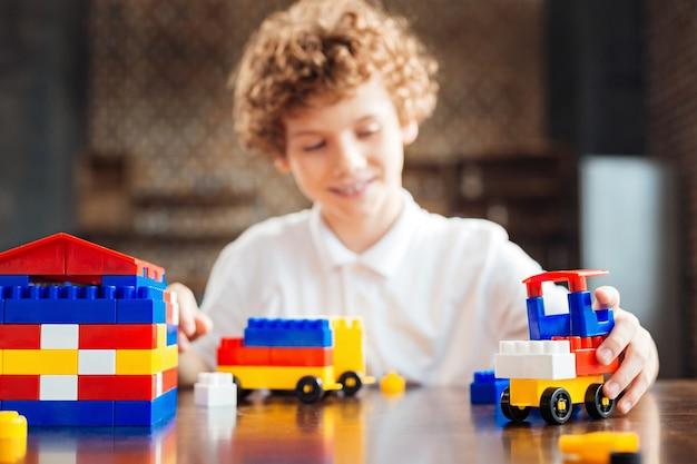 Messa a fuoco selettiva su una casa colorata in piedi su un tavolo e un'auto creativa guidata da un ragazzo sorridente che trascorre il suo tempo libero a casa e gioca con un set di costruzioni.