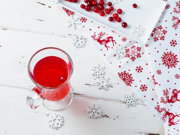Messa a fuoco selettiva sui mirtilli rossi in una bevanda fresca in una tazza di vetro. bacche su un piatto di ceramica rettangolare bianco, un tovagliolo con ornamenti di capodanno e fiocchi di neve sul tavolo.