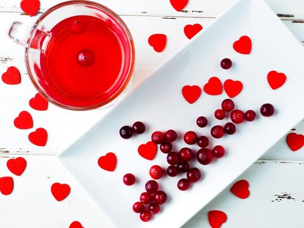 Messa a fuoco selettiva su mirtilli rossi e cuori rossi su un piatto rettangolare bianco
