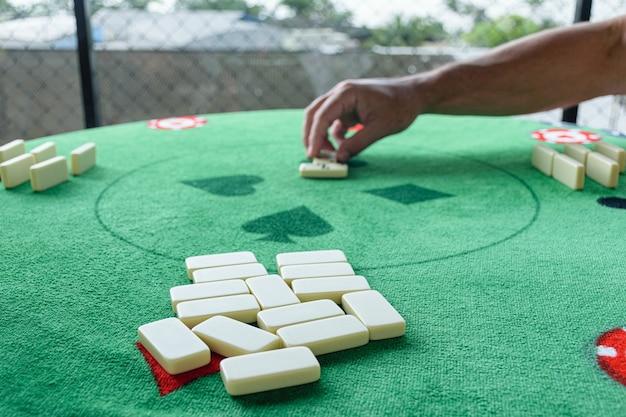 Messa a fuoco selettiva sui pezzi del domino in primo piano. sullo sfondo, l'uomo inizia il gioco.