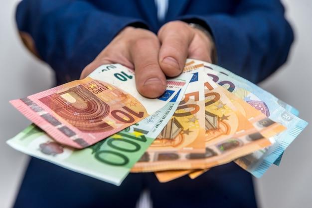 Messa a fuoco selettiva delle banconote in euro nelle mani degli uomini