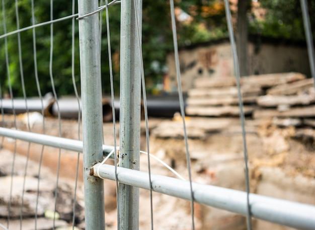 Messa a fuoco selettiva della recinzione intorno alla trincea con tubi dell'acqua isolati e lastre di cemento all'aperto. concetto di infrastruttura fognaria urbana, ammodernamento e ricostruzione del sistema sotterraneo.