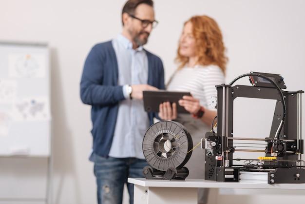 Messa a fuoco selettiva di un filamento collegato alla stampante 3d mentre viene utilizzato per la creazione di modelli 3d