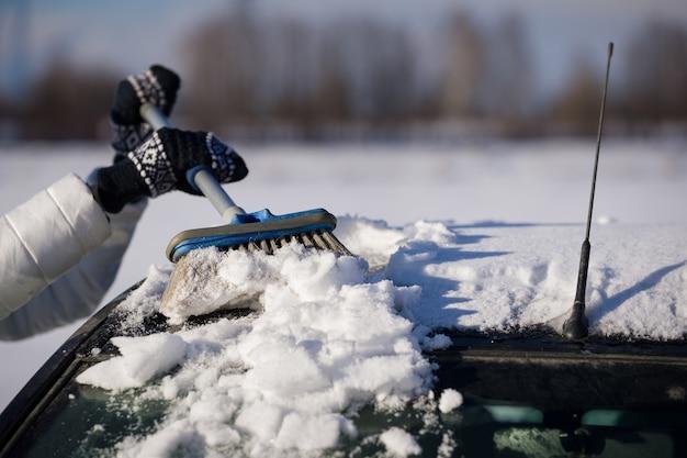 Messa a fuoco selettiva di una spazzola soffice nelle mani di una ragazza che pulisce il tetto di un'auto dalla neve