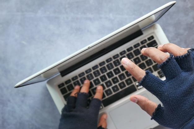 Messa a fuoco selettiva. mano di hacker che ruba i dati dal laptop dall'alto verso il basso.