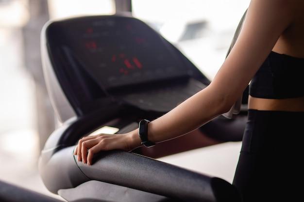 Messa a fuoco selettiva mano di giovane donna sexy che indossa abbigliamento sportivo e smartwatch in piedi sul tapis roulant per impostare il programma per l'allenamento in palestra moderna, copia spazio