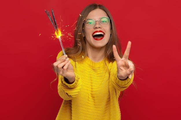Messa a fuoco selettiva della donna felice che tiene le stelle filanti e che mostra il segno di pace