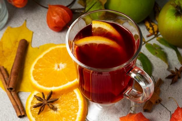 Messa a fuoco selettiva, bevanda calda, vino rosso riscaldato con frutta di arance e mele, con spezie di anice e cannella