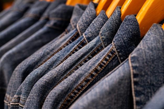 Fuoco selettivo sui jeans della giacca che appendono sulla cremagliera nel negozio di vestiti.