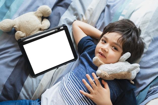 Messa a fuoco selettiva kid posa a letto giocando con peluche, bambino sdraiato a letto con tablet, vista dall'alto bambini che hanno attività per conto proprio in camera da letto con tavoletta digitale.