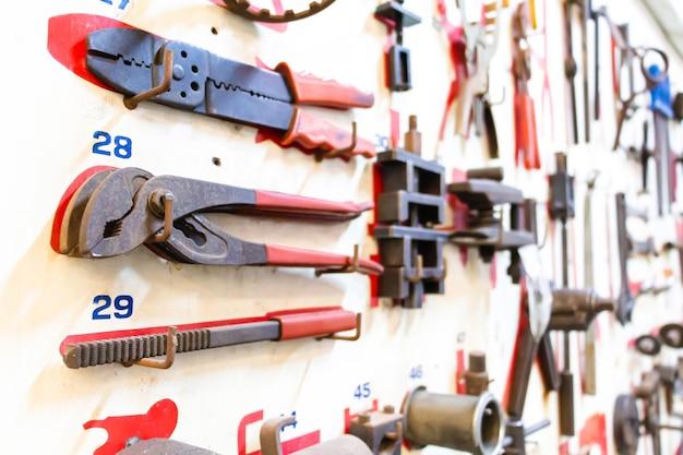 Strumenti di layout di messa a fuoco selettiva del tecnico su tavola di legno bianca. riparazione attrezzature e molti strumenti utili. kit di strumenti di riparazione.
