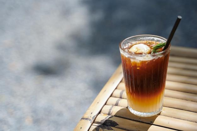Messa a fuoco selettiva caffè nero lungo mescolato con litchi. menu di bevande ghiacciate di drink estivi per una giornata di relax.