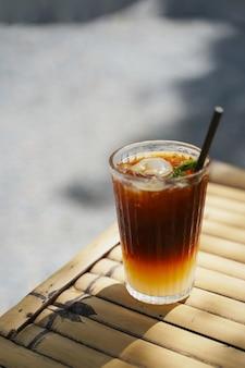 Messa a fuoco selettiva caffè nero lungo mescolato con litchi sullo sfondo della natura. menu di bevande ghiacciate di drink estivi per una giornata di relax.