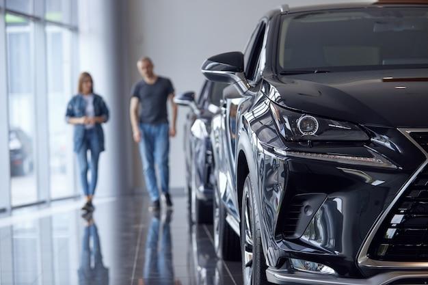 Messa a fuoco selettiva di un'auto di lusso di lusso sullo sfondo di una coppia sposata che sceglie un'auto