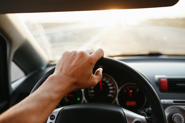 Messa a fuoco selettiva la mano dell'uomo sul volante, guidando un'auto al tramonto. sfondo di viaggio.