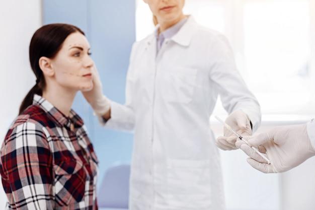 Messa a fuoco selettiva di una siringa medica che viene data a una bella dottoressa professionista durante un'operazione di cosmetici
