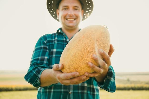 Messa a fuoco selettiva sul melone contadino caucasico tiene in mano un melone il suo tempo di raccolta