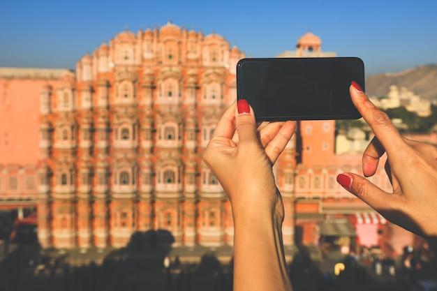 Fuoco selettivo sul telefono del moblie che prende immagine di hawa mahal (palazzo del vento) a jaipur, india