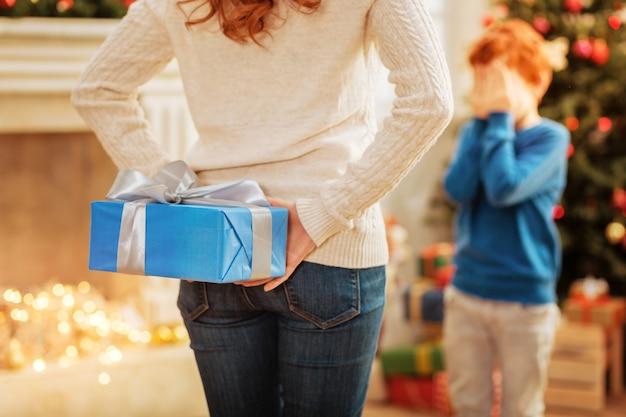 Messa a fuoco selettiva su una madre che indossa abiti casual che nasconde un regalo di natale splendidamente avvolto dietro la schiena