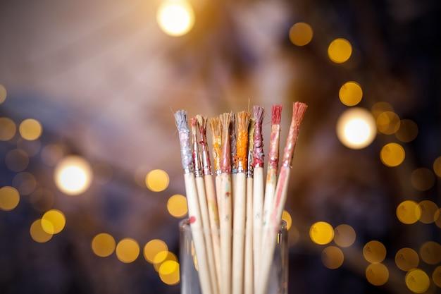 Messa a fuoco selettiva dei pennelli da pittura, molti pennelli diversi con resti di vernici diverse