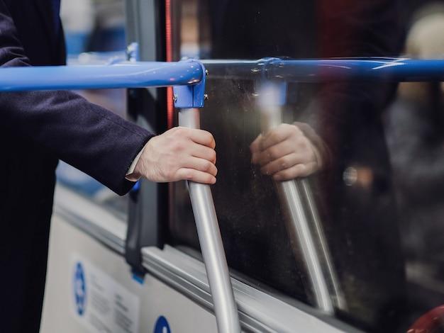 Messa a fuoco selettiva sulla mano maschile di un passeggero che tiene un corrimano nel trasporto pubblico.