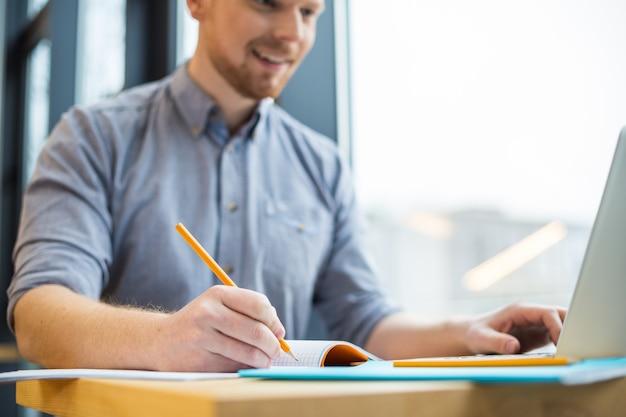 Messa a fuoco selettiva di una matita utilizzata da un uomo simpatico positivo mentre prende appunti