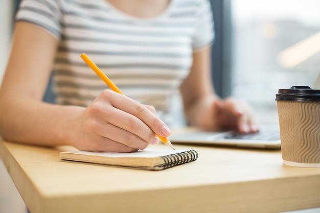 Messa a fuoco selettiva di una matita utilizzata durante la scrittura di note sul taccuino
