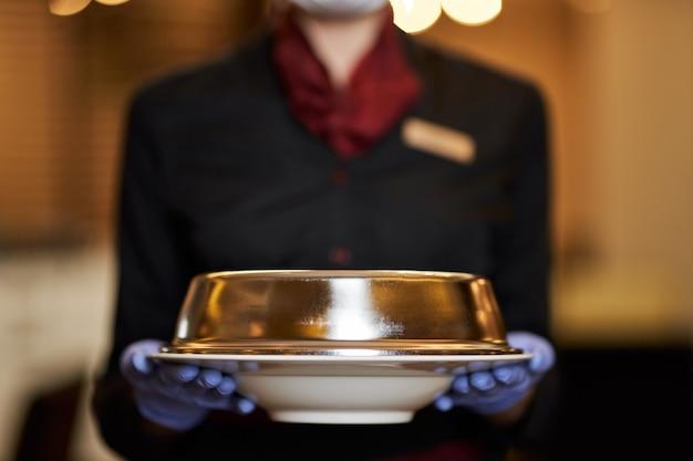 Foto di messa a fuoco selettiva del piatto coperto nelle mani della cameriera