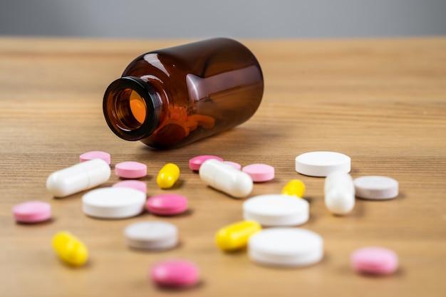 Messa a fuoco selettiva sulla pillola diffusa su sfondo di legno. concetto di assistenza sanitaria globale. industria farmaceutica. farmaci in contenitore medico su fondo in legno.