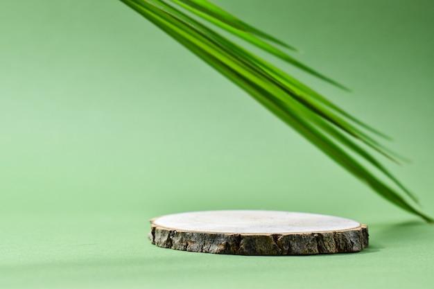Messa a fuoco selettiva. podio per la presentazione del prodotto. una scena minimalista di un albero abbattuto si trova su uno sfondo verde.
