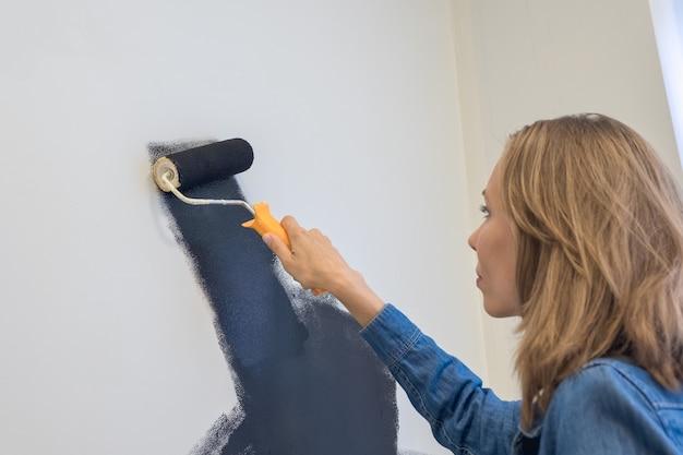 Messa a fuoco selettiva. la bella donna con un rullo dipinge il muro di nero. concetto di riparazione domestica. copia spazio.