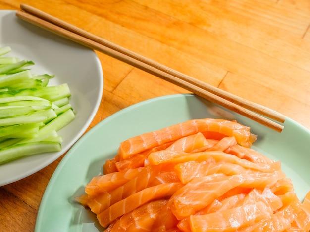 Messa a fuoco selettiva su fette di salmone e cetriolo fresco su piatti e bacchette