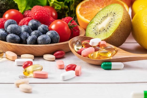 Messa a fuoco selettiva di frutta e verdura fresca con medicine diverse su un cucchiaio di legno