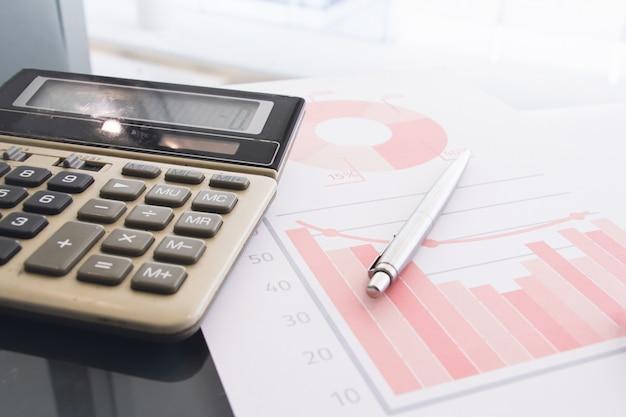Penna d'argento con messa a fuoco selettiva, calcolatrice su carta statistica o grafico. concetto di informazioni o dati. conto o concetto finanziario.