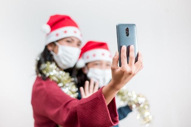 Videochiamata smart phone con messa a fuoco selettiva sul coronavirus natalizio.