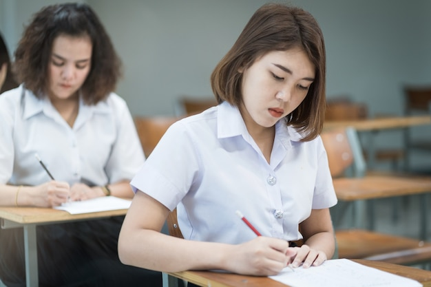 Il fuoco selettivo degli studenti universitari adolescenti si siedono sulla sedia della lezione, scrivono sul foglio di risposta della carta d'esame prendendo la stanza dell'esame finale o l'aula. studenti universitari in uniforme in aula.