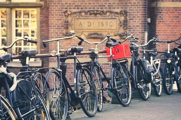 Messa a fuoco selettiva sulla tradizionale bicicletta olandese parcheggiata sul canale di amsterdam, paesi bassi
