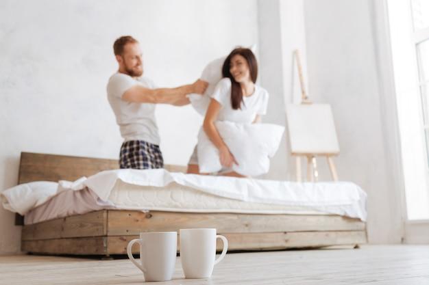 Messa a fuoco selettiva su due tazze e una giovane coppia radiosa che si picchiano a vicenda con i cuscini a letto dietro