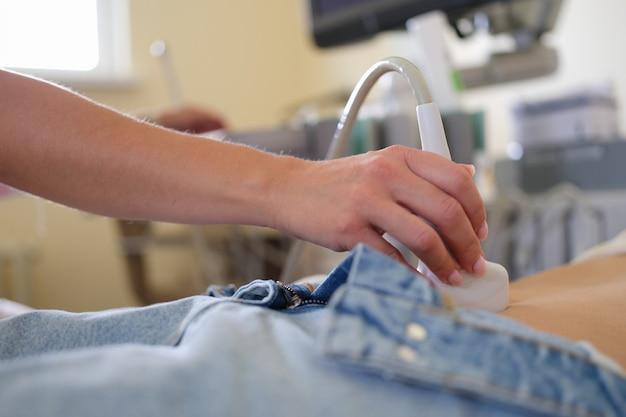 Messa a fuoco selettiva sul dispositivo scanner a ultrasuoni in mano al medico professionista che esamina il paziente