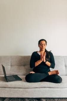 Messa a fuoco selettiva un ritratto verticale di donna latina seduta a fare yoga guardando una lezione online al chiuso. yoga a casa concetto. copia spazio