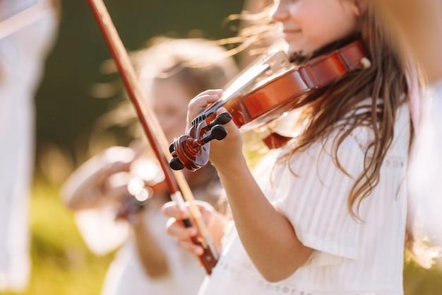Messa a fuoco selettiva al violino di una giovane bambina che suona all'aperto durante il festival estivo.