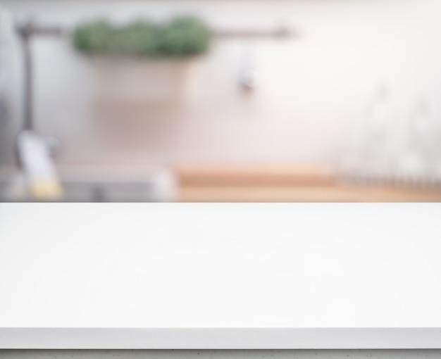 Messa a fuoco selettiva / piano del tavolo bianco sul bancone della cucina sfocato