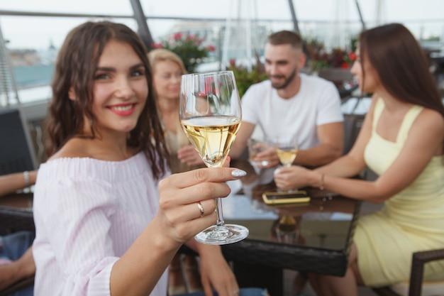 Messa a fuoco selettiva su un bicchiere di vino nella mano di una donna allegra che beve con gli amici