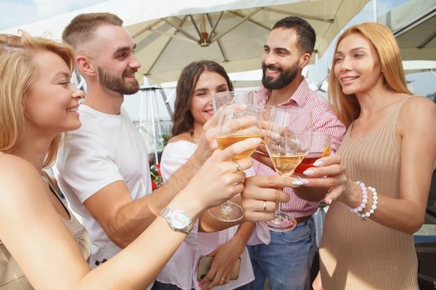 Messa a fuoco selettiva sui bicchieri di vino nelle mani di un gruppo di amici che tostano durante la festa