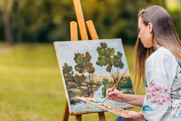 Messa a fuoco selettiva su una donna seduta sulla schiena mentre dipinge su una tela in un parco.