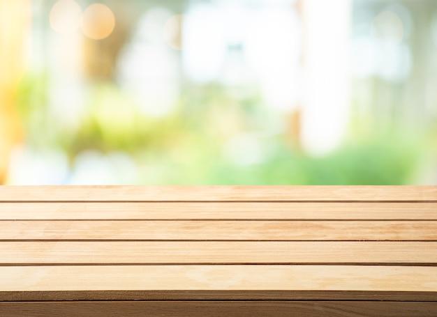 Messa a fuoco selettiva piano del tavolo in legno su sfocatura dello sfondo della parete di vetro astratta.
